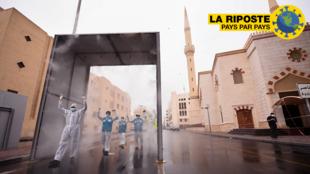 Des soignants volontaires passent un portique de stérilisation installé pour désinfecter chaque personne qui entre ou qui sort du quartier de Naif à Dubaï, le 15 avril 2020.