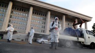 Des agents désinfectent les abords de l'Assemblée nationale à Séoul le 24 février 2020.