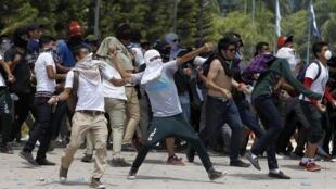 Estudiantes arrojan piedras a la policía durante una manifestación en Tegucigalpa, el 25 de marzo de 2015.