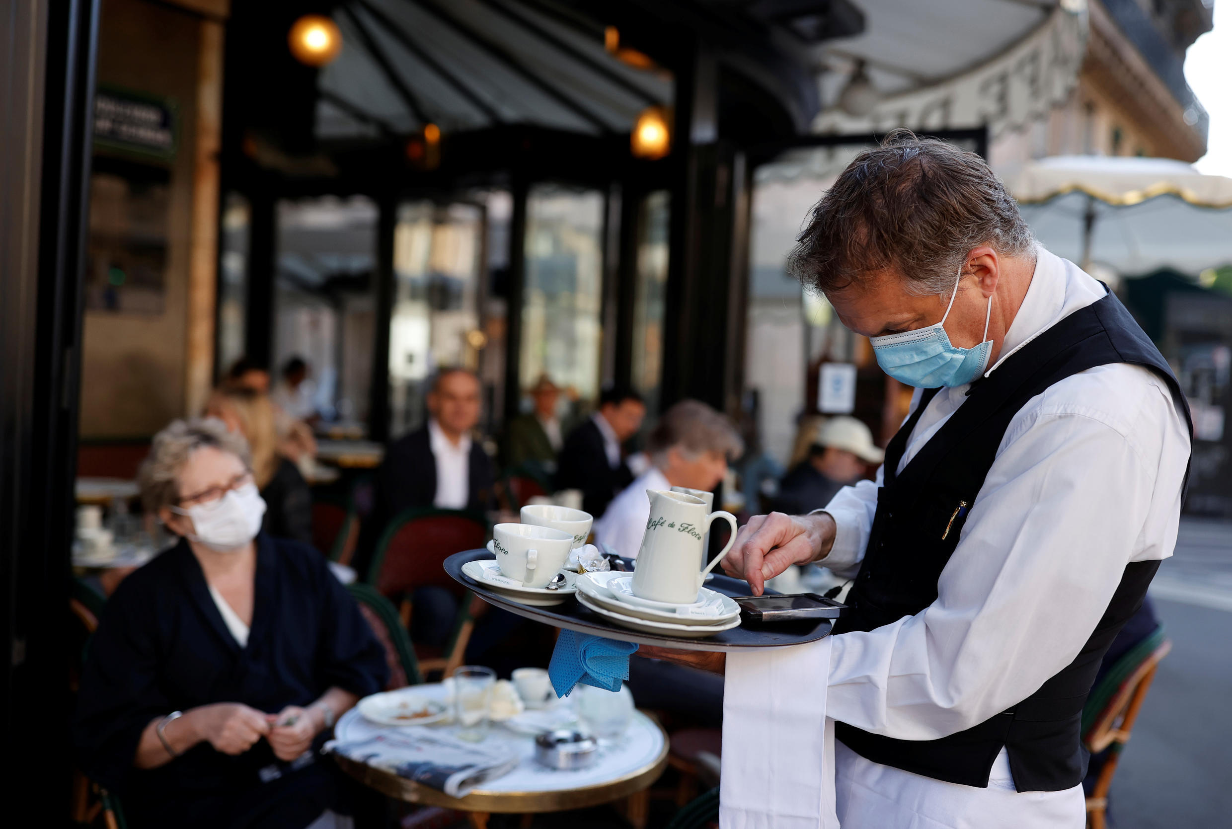 A waiter wearing a face mask serves customers at Cafe de Flore, in Paris on 2 June, 2020.
