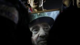 Un hombre carga la foto de Fidel en el multitudinario homenaje en Santiago de Cuba.