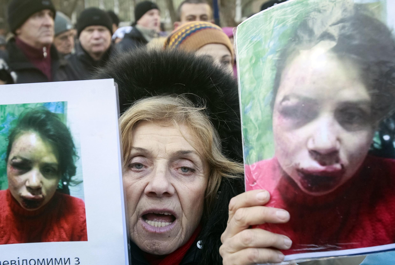 В Киеве протестующие держат плакат с изображением избитой журналистки Татьяны Черновол
