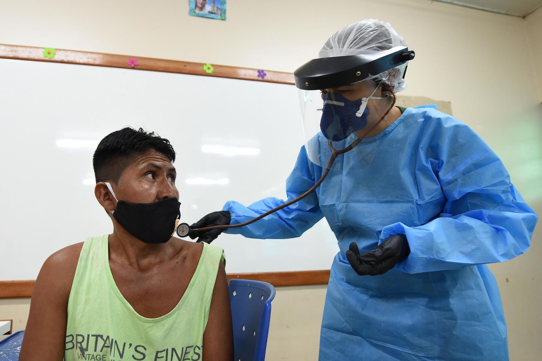 Un membre de l'ethnie Marubo passe une visite médicale avec un médecin des forces armées brésiliennes à Atalaia do Norte, dans l'État de l'Amazonas au nord du Brésil, le 20 juin 2020.