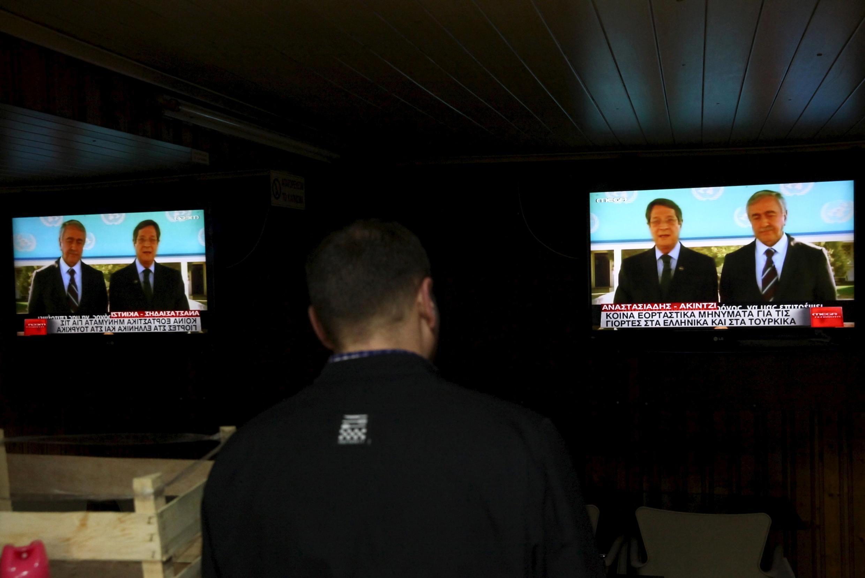 Un homme regarde les deux dirigeants chypriotes s'exprimer ensemble à la télévision à la veille de Noël, le 24 décembre 2015.