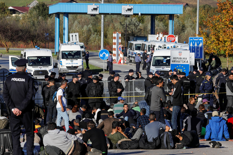 Des garde-frontières bosniens et croates face à des migrants, à Maljevac, le 24 octobre 2018.