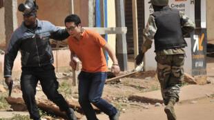 An ninh Mali sơ tán một người ra khỏi khu vực gần khách sạn Radisson Blu, ở Bamako, ngày 20/11/2015