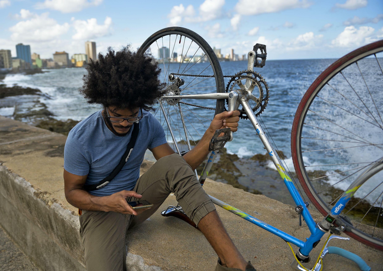 El cubano Yasser González usa su celular para conectarse a internet en el malecón de La Habana, Cuba, el 24 de noviembre de 2020