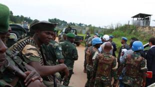 Desemba 3, 2014. Wilayani Beni, DR Congo. Askari wa jeshi la DRC, FARDC, na walinda amani mbele ya makao makuu ya MONUSCO, Beni.