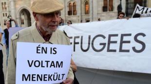 """Senhor com um cartaz: """"Eu também fui refugiado"""", durante manifestação de ativistas em frente ao parlamento em Budapeste. Protesto contra a política de migração do governo Orban, em 30 de setembro, 2016."""