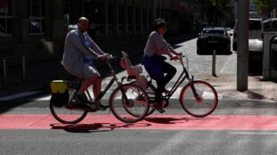 Casal de ciclistas nas ruas de Bruxelas, em 06.05.2020