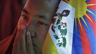 A Tibetan monk holds a flag as he takes part in a day-long hunger strike in New Delhi 19 October, 2011.