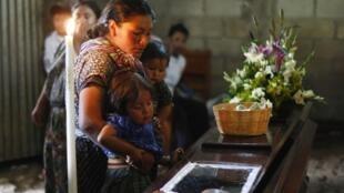 Dominga Zet mira el cuerpo de su marido fallecido, Justo Racxon Chocón, con sus hijos, este 21 de septiembre.
