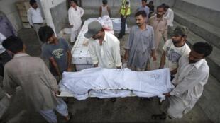 Une famille transporte le corps d'un des leurs, tué par un sicaire non identifié dans les rues de Karachi ce 27 juillet 2011.