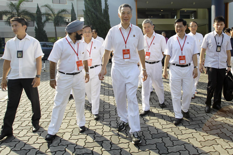 លោកនាយករដ្ឋមន្រ្តីសិង្ហបុរី Lee Hsien Loong (រូបកណ្តាល) ដើរជាមួយបេក្ខជនរបស់គណបក្សសកម្មភាពប្រជាជន នៅថ្ងៃបោះឆ្នោត នៅសិង្ហបុរី នៅថ្ងៃសៅរ៍ទី ៧ ឧសភា ២០១១