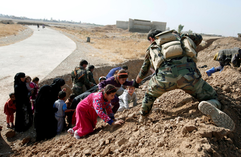 Combatentes peshmerga curdos ajudam mulheres e crianças iraquianas que fogem da aldeia de Abu Jarboa 31 de outubro de 2016.