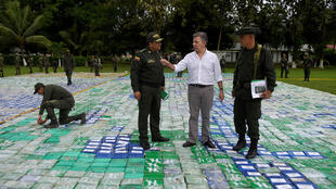 Presidente de Colombia, Juan Manuel Santos, caminha sobre o carregamento de cocaína descoberto pela polícia.