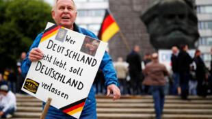 """Um manifestante em Chemnitz, no leste da Alemanha, durante um protesto da extrema direita, em setembro de 2018, mostra um cartaz com os dizeres: «Quem não ama a Alemanha deveria deixar o país""""."""