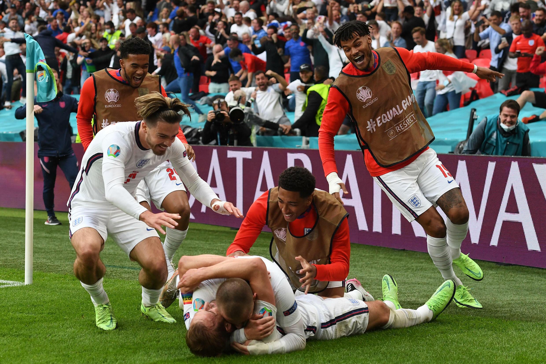 L'attaquant anglais Harry Kane (c, à terre) est félicité par ses coéquipiers, après avoir marqué le 2e but face à l'Allemagne, lors de leur 8e de finale de l'Euro 2020, le 29 juin 2021 au stade de Wembley à Londres