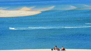 """People enjoy a sunny day atop Europe's tallest sand dune, the """"Dune du Pilat"""", after its reopening in La Teste-de-Buch, France"""