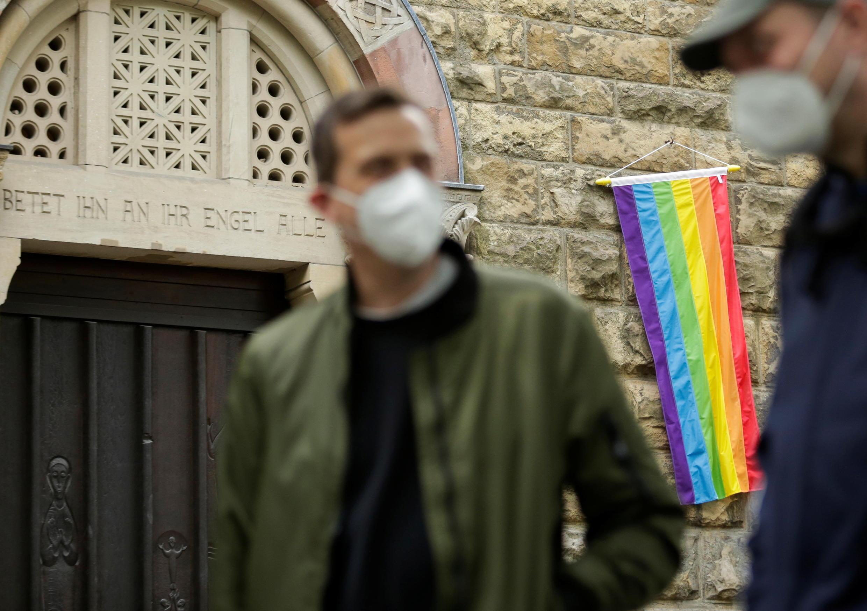 Unas personas se paran frente a una bandera arcoíris en la pared de una iglesia católica mientras el edificio está abierto para que las parejas del mismo sexo reciban una bendición en Colonia, Alemania, el 10 de mayo de 2021. REUTERS/Thilo Schmuelgen