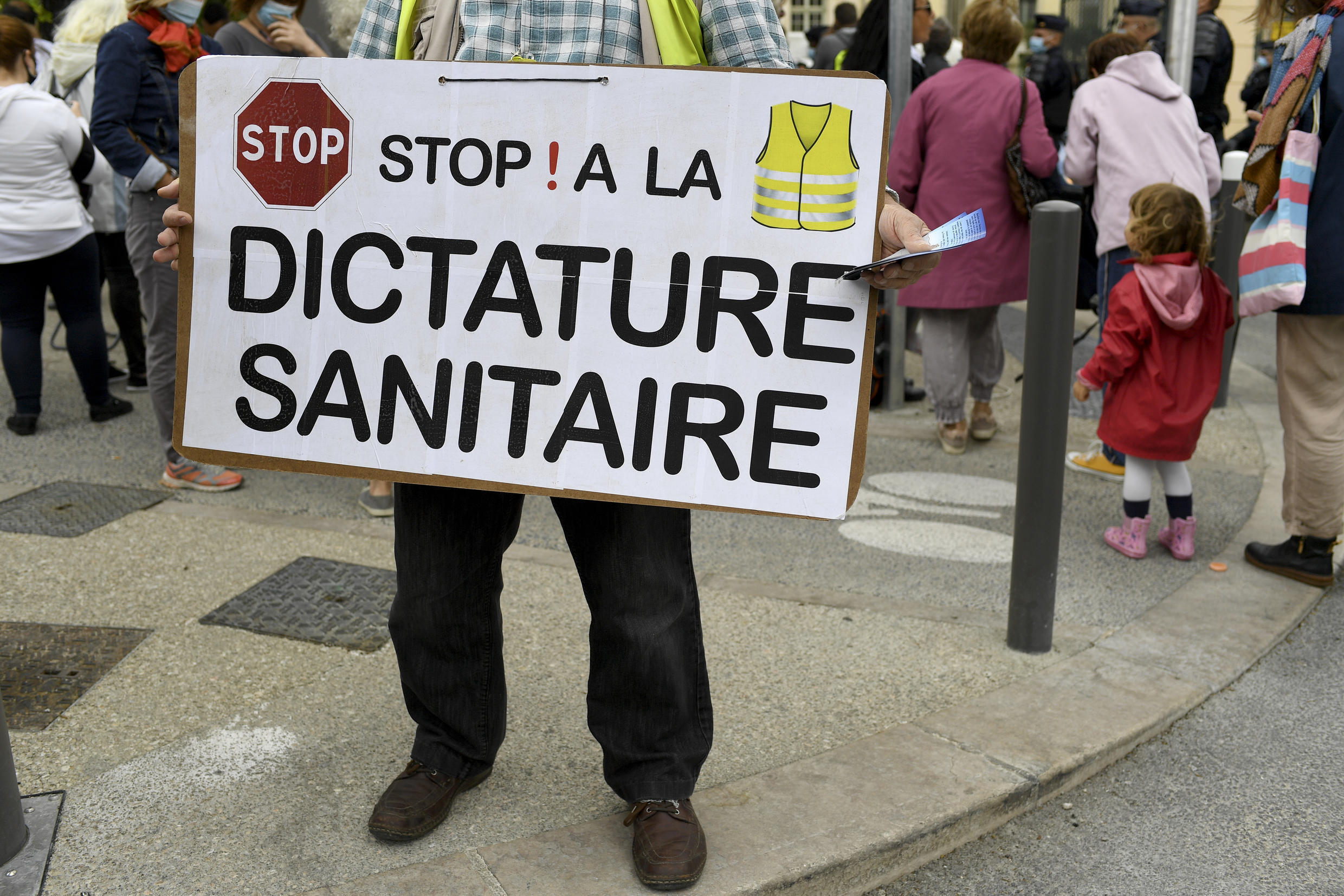 """A protesters wearing a yellow vest holds a placard reading """"Stop ! to sanitary dictatorship"""" during a demonstration by bar and restaurant owners against new shutdown orders to curb a surge in Covid-19, September 25, 2020."""