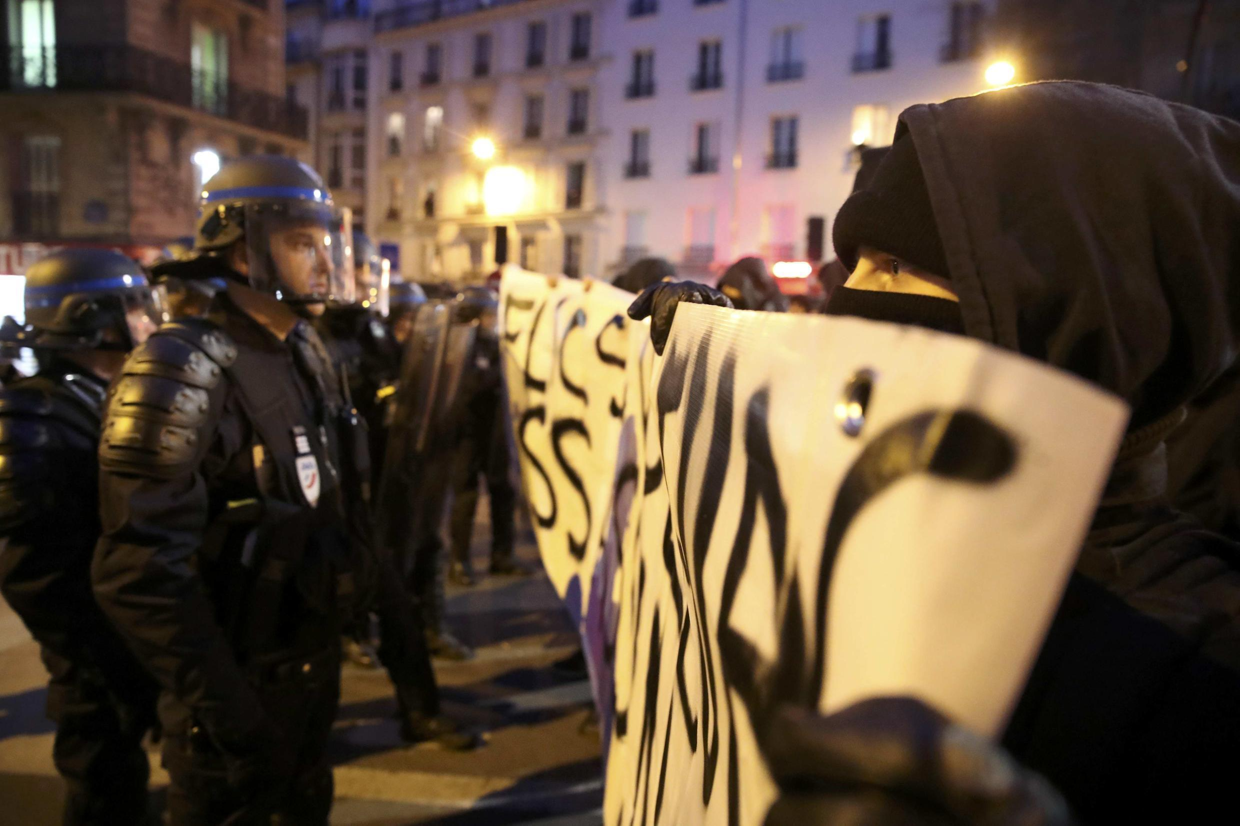 """French riot police face off with people holding a banner reading, """"Cops rapists murderers"""" on a protest last week"""
