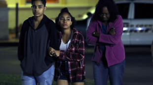 People walk out of a hotel where students were quickly taken after a mass shooting at the Marjory Stoneman Douglas High School where at least 17 people were killed, on February 14, 2018 in Parkland, Florida