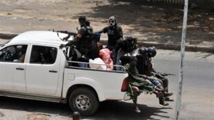 Des miliciens pro-Gbagbo patrouillent dans les rues désertées d'Abidjan, jeudi 31 mars 2011.