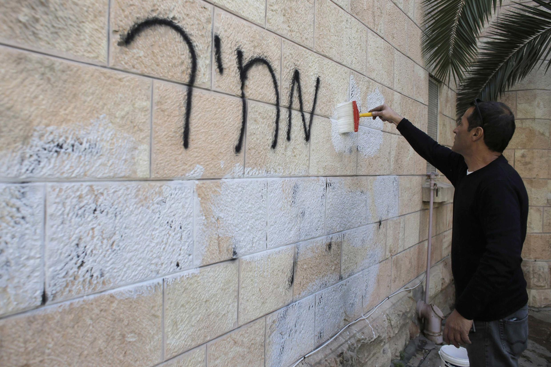 Un employé municipal efface un tag raciste sur le mur d'une église orthodoxe roumaine à Jérusalem, le 9 mai 2014.