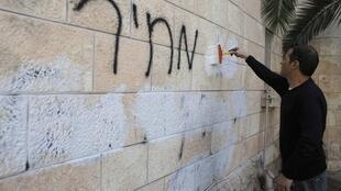 Un empleado municipal borra un grafiti racista en la pared de una iglesia ortodoxa rumana, en Jerusalén, el 9 de mayo de 2014.
