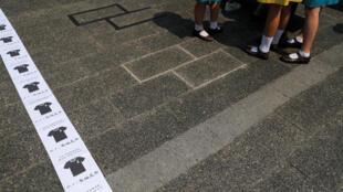 Des étudiants rassemblés à côté de pancartes collées au sol appellent à porter du noir en signe de deuil le 1er octobre qui célèbre le 70e anniversaire de la Chine communiste. (Photo du 29/09/2019 à Hong Kong)