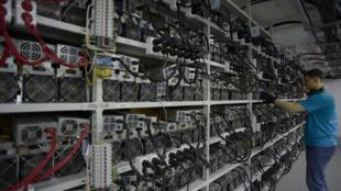 """Un empleado inspecciona máquinas para la producción de bitcoins y lightcoins en el centro minero """"Kriptounivers"""" (CryptoUniverse) durante una presentación del centro de criptomonedas más grande de Rusia, en Kirishi, el 20 de agosto de 2018."""