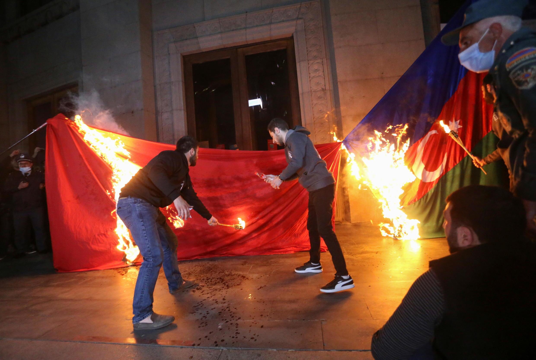 Участники шествия в годовщину армян сжигают турецкий и азербайджанский флаги. Ереван, Армения. 23 апреля 2021 г.