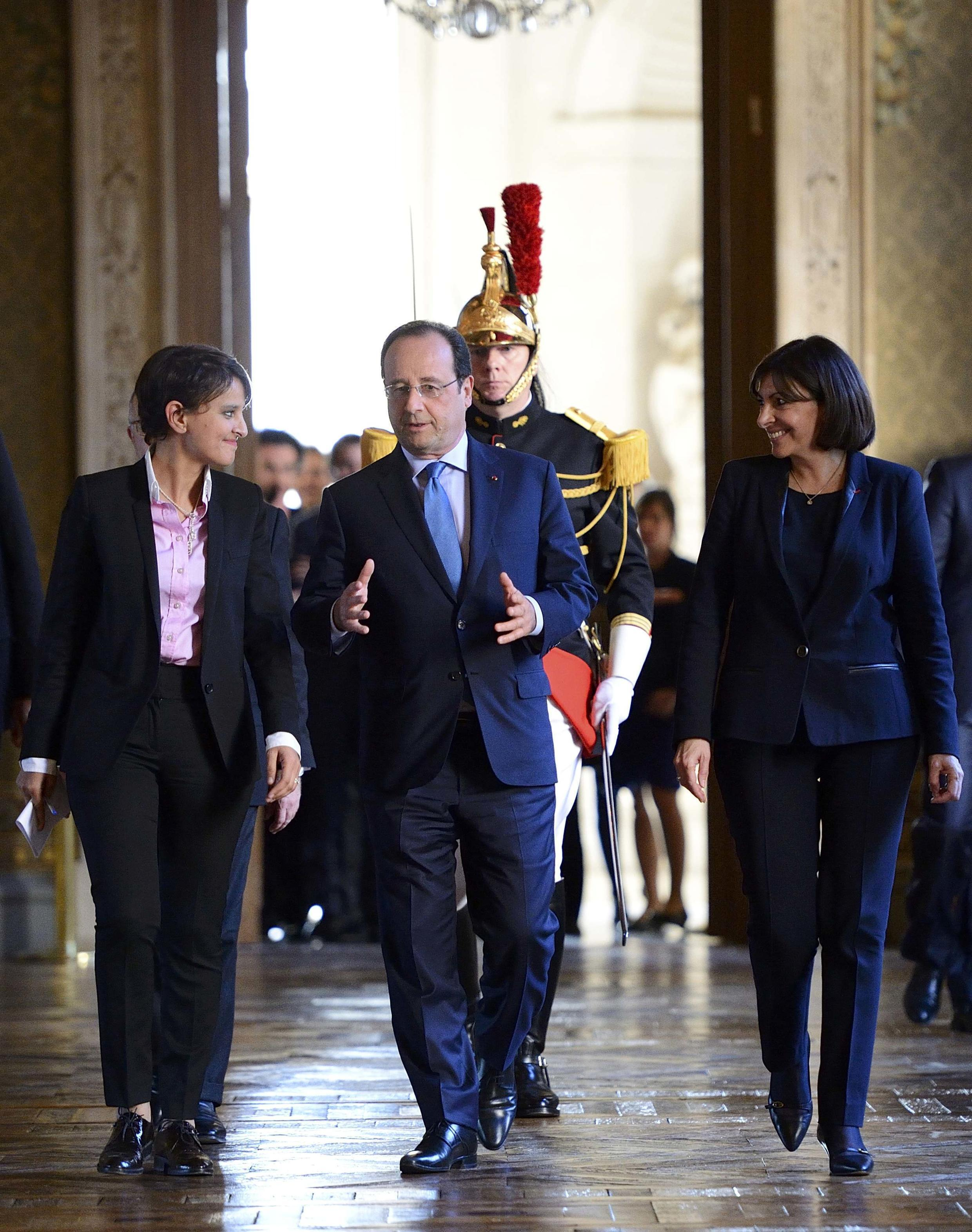 French President Francois Hollande (C) speaks with French Minister for Women's Rights Najat Vallaud-Belkacem (L) and Paris Mayor Anne Hidalgo (R) at the Paris town hall