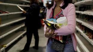 Pessoas fazem compras; comida e outros itens em um supermercado em Caracas.