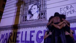 Le 15 mars 2018, des jeunes se consolent auprès d'un portrait dessiné de Marielle Franco, conseillère municipale de Rio de Janeiro assassinée.