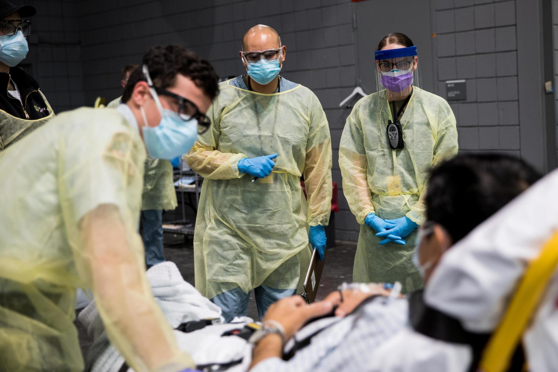Des soldats affectés au Javits New York Medical Station effectuent des procédures d'enregistrement sur un patient atteint de coronavirus avec des travailleurs d'urgence locaux dans la baie médicale de l'établissement à New York City, États-Unis.