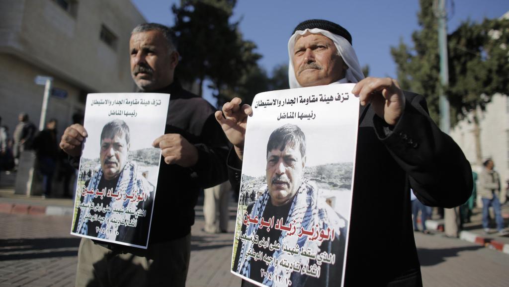 Raia wa Palestina waandamana wakiwa na mabango yenye picha ya waziri Palestina, Ziad Abu Ein, aliyeuawa Jumatano Desemba 10 mwaka 2014.