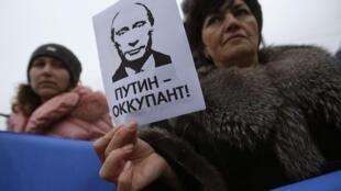 """Một người biểu tình tại Simferopol ngày 11/03/2014 với tấm bảng mang dòng chữ """"Putin – Kẻ chiếm đóng""""."""
