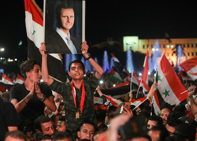 Wasyria wanakishikilia bendera ya nchi na picha ya Bashar al-Assad Mei 27, 2021 huko Damascus, siku moja baada ya uchaguzi wa rais ambao alitngazwa mshindi