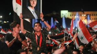 Des Syriens brandissent des drapeaux nationaux et le portrait de Bachar al-Assad le 27 mai 2021 à Damas, au lendemain de l'élection présidentielle pour laquelle il est donné vainqueur