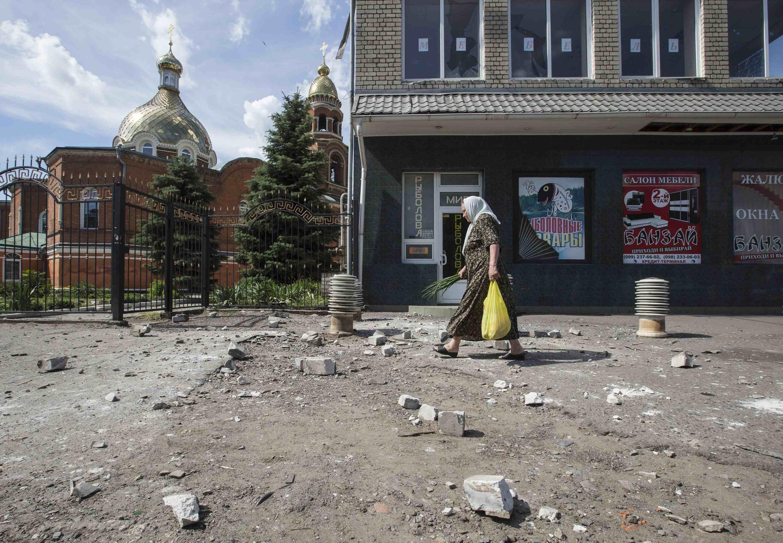 Mulher atravessa uma rua em Slaviansk, no leste da Ucrânia, depois de bombardeios.