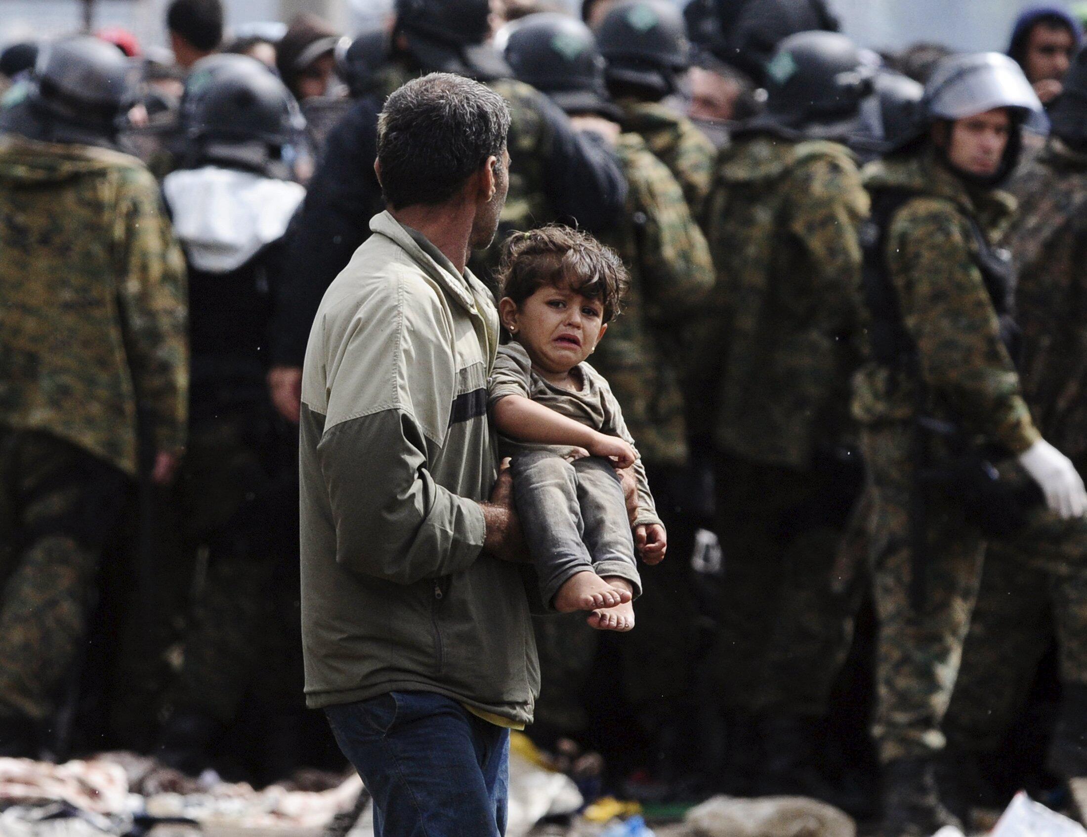 Мужчина с ребенком после пересечения границы Греции с Македонией, 22 августа 2015 г.