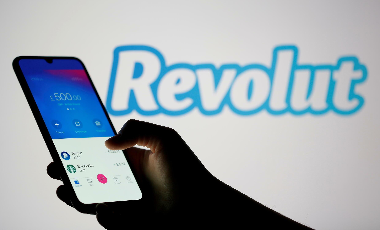 Main d'une personne tenant son smartphone au fond il y a un logo Revolut.