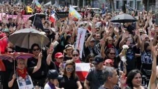 Des manifestants marchent vers le palais présidentiel de La Moneda à Santiago, le 18 janvier 2020, pour protester contre le gouvernement chilien.