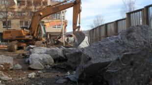 Des bulldozers s'attaquent au mur qui coupe la ville de Mitrovica en deux, au Kosovo, le 5 février.