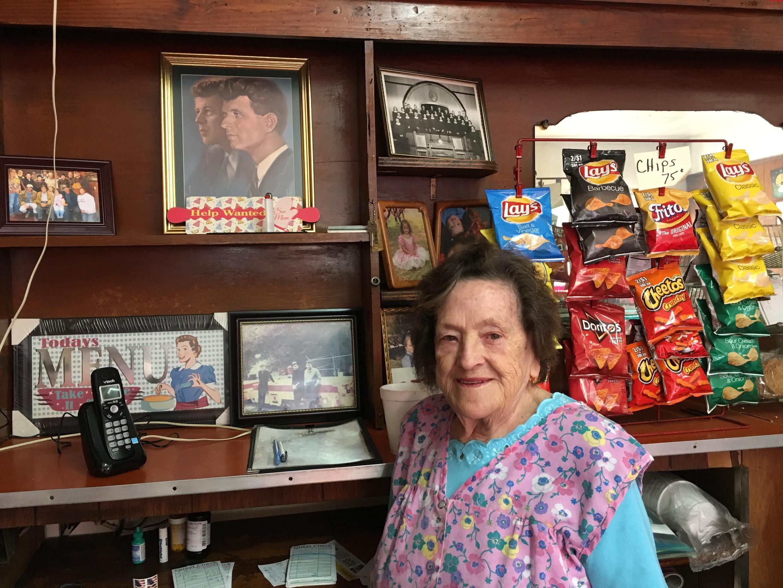 Orby Campbell, dans son café, devant la photo des frères Kennedy.