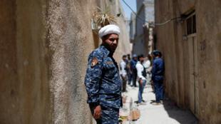 Un religieux chiite irakien avec la police fédérale sur la ligne de front dans la vieille ville de Mossoul, le 28 juin 2017.