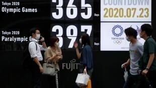 Des passants portant des masques protecteurs passent devant un écran montrant un compte à rebours des jours avant les Jeux olympiques de Tokyo 2020 à Tokyo, 23 juillet 2020.