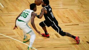Kyrie Irving (derecha), de los Brooklyn Nets, defendido por Aaron Nesmith, de los Boston Celtics, en el juego de playoffs del domingo.